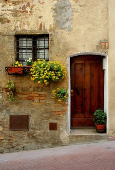 Tuscan towns, such as San Gimignano, epitomised by tiny coloured flowers climbing the cracked walls of old Italian buildings