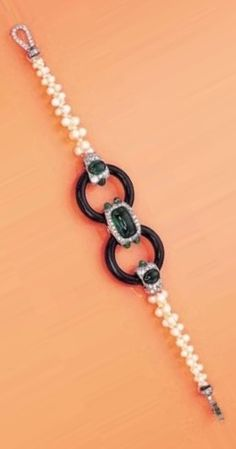 CARTIER - AN ART DECO GEM-SET BRACELET, CIRCA 1922. The central section set with a cabochon emerald in a single-cut diamond and emerald panel, flanked by black onyx hoops to the emerald and diamond tapered shoulders and graduated pearl mesh band, with French assay marks Signed by Cartier, numbered.