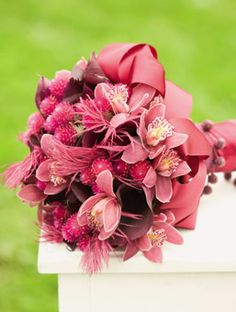 Calla Lily and Orchid Feathered Bouquet - Wine The ostrich feathers and gomphrena lend texture to this bouquet of Swaltzwalder calla lilies and mini burgundy cymbidium orchids with double-faced satin ribbon, $250, by Kim Hirst for Michelle Rago, Ltd., 212-736-0195, michelleragoltd.com.