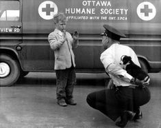 What does your little dog look like? Albert Clarmo of the Ottawa Humane Society, is preparing to return a lost puppy to a young boy, 1959.