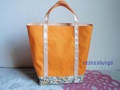 オレンジ色の帆布で、水筒とパン2個入るサイズを、との職場の同僚のリクエストの下作ったものです。鮮やかオレンジに、ベージュのサテンリボンとリバティプリントで中和...|ハンドメイド、手作り、手仕事品の通販・販売・購入ならCreema。