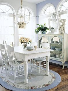The arched windows, pale blue on the wall and pretty floral rug, and the antique white furniture make this a relaxing and romantic dining space.
