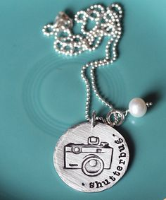 "Beautiful photographer's necklace! <3 (you can have anything you want put on it where ""shutterbug"" is)"