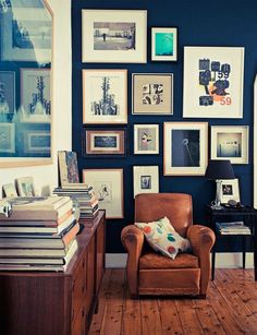 Love this picture wall and worn leather against the blue wall