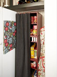 """No pantry? No problem. Designate a niche next to your refrigerator as food staple central. Fill the space with shelves (a bookcase works well) and hang a tension curtain rod between the wall and the refrigerator, decked out with a curtain to match your kitchen decor."""