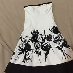 Black and white dress White dress with black trim and embroidered flower accents. Size 4 from White House black market. Has cotton lining. Small blue mark near right hip. Has loops for belt but I don't have the belt. Blue mark is barely noticeable. Loops could be cut off or any black belt could be a great accessory for this dress. White House Black Market Dresses Strapless