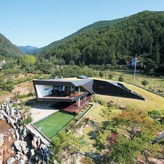 A cedar-clad house near Seoul by Korean architects AND spirals up from beneath the ground.