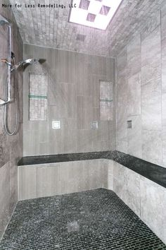 a modern walk in shower with a large shower bench and black tile floors click