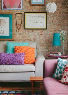 Sala de estar com parede de tijolinho e muitas cores nos acessórios de decoração.