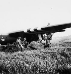 Airborne troops of 6th Airlanding Brigade, 6th Airborne Division, hitching a trailer to a jeep which has just been off-loaded from a Horsa glider (LH344 'Charlie's Aunt') on DZ 'N' near Ranville, on the evening of 6 June 1944.
