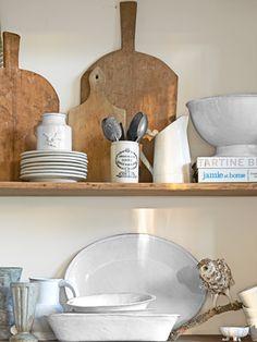 Old maple bread boards, made in the Loire Valley, share shelf space with fine Astier de Villatte porcelain in the breakfast nook's cabinet.