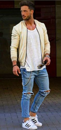 Choose a yellow bomber jacket and blue ripped skinny jeans for a trendy and easy going look. Complement this look with white leather low top sneakers.   Shop this look on Lookastic: https://lookastic.com/men/looks/bomber-jacket-tank-skinny-jeans/13652   — Yellow Bomber Jacket  — Grey Tank  — Silver Watch  — Dark Brown Bracelet  — Blue Ripped Skinny Jeans  — White Leather Low Top Sneakers