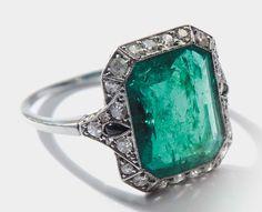 Anello Art Deco  montatura in platino con smeraldo centrale di ct 5,01. La pietra  contornata da piccoli diamanti e due gocce in smalto nero. 1920-1930