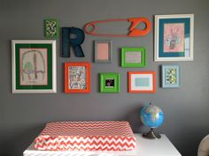 Orange, Green and Teal Gallery Wall over a changing table in a nursery