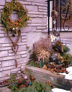 Creative winter protection of raised bed turns to display at entrance with plate rack repurposed trellis holding mini wreaths, twig heart lays down to resemble bird nesting, old coconut and enlarged pinecones clustered amongst mulching boughs, watched over by angels.