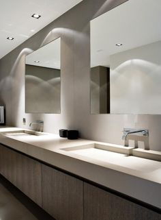 Sleek bathroom in neutral tones with extra large sinks in corian _