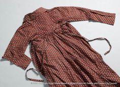 A day or walking dress made of printed cotton, with small spots of white with a blue surround on a red background. The dress is long-sleeved with a slight train to the skirt and an open apron front that ties at the back. 1808-1810 - Royal Albert Memorial Museum & Art Gallery, Exeter