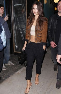 Emily Ratajkowski dresses up harem pants with a suede jacket and sandals.