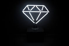 Desktop Diamond $99.99 USD The glowing white, hand crafted glass diamond stands atop a sturdy base made of high quality black acrylic. Perfect for a desk, shelf, table, ledge or windowsill. Your neon diamond has a 6 foot power cord, an on/off switch, and is connected to a UL certified transformer, which is housed inside the acrylic base.