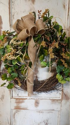 Handmade item Materials: grapevine wreath, glue, wire, wired burlap, realistic fern, realistic greenery Made to order Ships from United States Questions? Contact shop owner Item details This beautiful burlap front door greenery wreath is the perfect simple accent for your door or interior. A wired burlap ribbon makes a simple bow. FRONT DOOR WREATH. This wreath could also be for the fall. Such pretty fall green foliage. Average Diameter: 22 (tip to tip) This wreath will be created on a g...