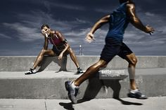 Male athlete running with a female athlete resting on steps and wiping her face