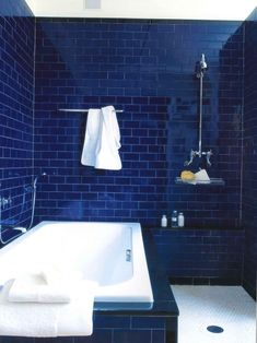 A great deep blue bath tiled from floor to ceiling creates a memorable space. The crisp white floor tile anchors the bath and ties back to the white fixtures.