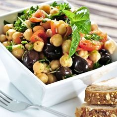 Nutty chickpeas are tossed with black olives, red onion, tomatoes and a basil vinaigrette for a flavorful and easy-to-make summer side dish.