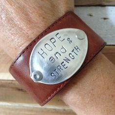 A reminder that there is hope and you have the strength! This leather cuff is crafted from upcycled leather and a vintage silver plated spoon and has one snap