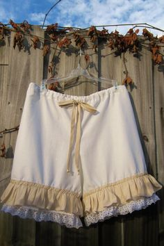 I called these bloomers but they are shorts gathered on the legs. Back in the old days, ladies wore these as undergarments but you can wear yours anyway you want. I love the antique look of these shorts. They have a ruffle in light tan cotton fabric and a lace trim at the hem. The legs have a very light elastic that is comfortable. Waist has a elasticized drawstring that you can adjust to your waist. Also, waist sits slightly below the belly.button Inseam is about 5 inches. I can also make…