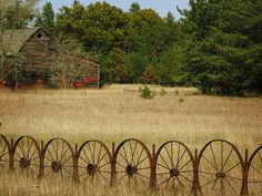 A wagon wheel fance with an old red barn across the pasture