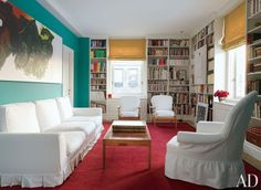 In the library of perfumer Frédéric Malle's New York apartment, white bookcases compliment the bold turquoise wall color and red carpet.