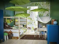 chambre enfant jungle sous de grandes feuilles vertes. Les couleurs naturelles et le papier peint végétal viennent compléter cette atmosphère à la fois intime et exotique.