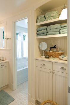 The bright white bathroom may be petite, but it has generous storage space and a small window to let in natural light. Beach Cottage Style, Beach Cottage Decor, Coastal Cottage, Coastal Decor, Beach House, Coastal Style, Lake Cottage, White Cottage, Cottage Ideas