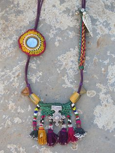 Kinship Stories: Necklace made with an elastic base. The tassels are vintage Uzbek. They come from a vintage hair adornment piece and from old tapestry. Around them are North African trade beads and Afghani triangular glass beads. The silver centerpiece is a Berber cross from Morocco (925 k). The embroidery with a mirror inside it is Rabari Indian. It comes from an old dowry bag. The longer embroidered piece comes from Uzbek tapestry, with Yemeni beads and a Nepali yak horn.