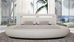 Off white leather creates a functional and stunning finish to this ultra modern bed. The soft rounded edges give a curved circular appearance to the bed but still mold in well with the rectangular bedhead. This piece of furniture makes  a dramatic statement and is  the main feature of this large room