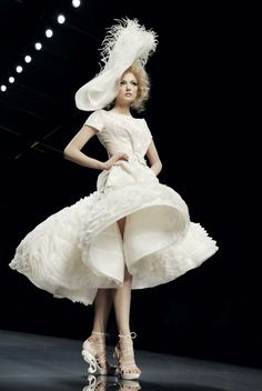 John Galliano...beautifully odd white dress. Sure, it's quite different, but it's composition and design is gorgeous.