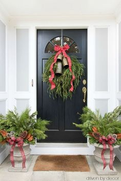 Simple front porch greenery to decorate for Christmas including a greenery swag with bells and a bow and planters filled with fresh greenery. Part of a beautiful Christmas home tour! #christmas #greenery #porch #frontdoor #wreath #swag #planters #bells