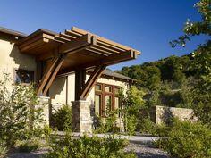 Современный одноэтажный дом из природных материалов расположенный у холма