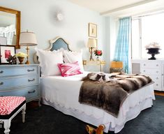 Sara Tuttle Interiors      Amazing bedroom with watery blue walls paint color, white & blue vinyl headboard, white scalloped bedding with pink trim, mismatched nightstands: blue French chest, gold console table, pink ikat pillow, faux fur throw, antique brass lamps, gold leaf framed mirror and blue silk curtains