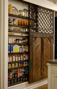 great use of a barn door for kitchen pantry, making the top storage area visible (colorful) & created by opening the space between the studs in the wall