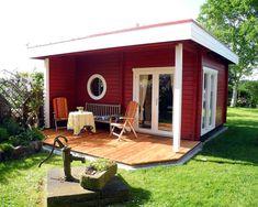Flachdach Gartenhaus in Schwedenrot mit gemütlicher Holzterrasse und vintage Wasserpumpe im Garten.
