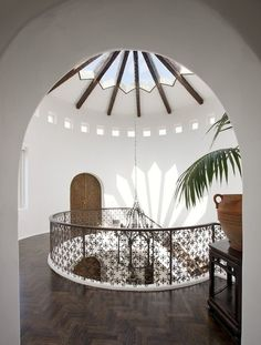 Spanish Style home with dome glass ceiling, iron staircase railing and wood floors in chevron herringbone pattern.