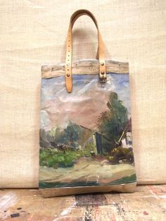 Painting Bag - Woods A series of unique, leather handled carry bags made by hand using vintage oil paintings sourced exclusively from markets in Holland and Belgium. Each bag tells its own story through the juxtaposition of timeworn painted canvases, making each one a distinctive piece of functional, wearable art. This series of carry bags are strong, versatile and spacious, and are designed to show signs of wear with use & age so that their stories live on.