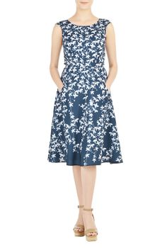 An elegant wide scoop neck tops our fit-and-flare crepe dress featuring a digital leafy vine print.
