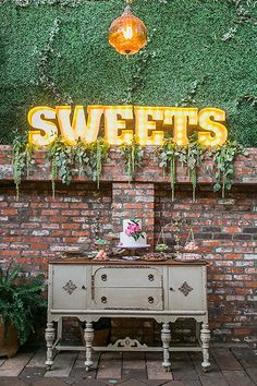 Let your cake table shine with some original décor. Swap it out for an antique desk and juxtapose it with a marquee sign to spotlight the display.Related: 25 Creative Ways to Show Off Your Wedding Cake