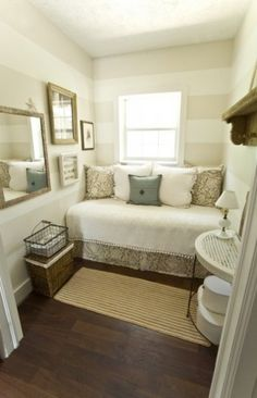 Idea for tiny guest bedroom: wall-to-wall daybed in corner, neutral horizontal stripes elongate room, mirror + small scale natural accessories make room feel bigger + cozy
