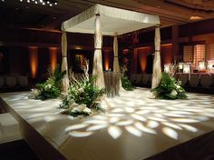 Fabric covering with legs clad in branches and atmospheric leaf lighting pattern.