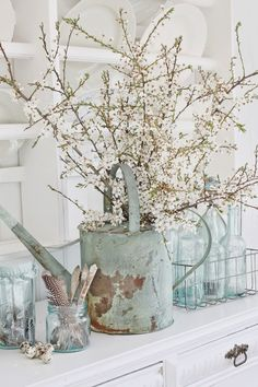 Old watering can turned into flower vase. Soft colors. Shabby chic.  Country chic