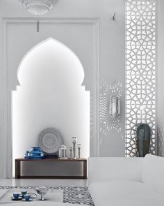 Mesmerizing Moroccan interior design - It is not unusual to find these types of arches in mosques. Here, they act as a lovely framing device for interesting art pieces.