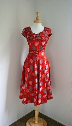 A richly crimson hued, endlessly beautiful 1950s satin brocade dress featuring a lovely chrysanthemum print.